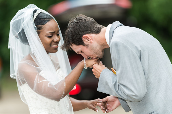 Groom kissing bride's hand at wedding