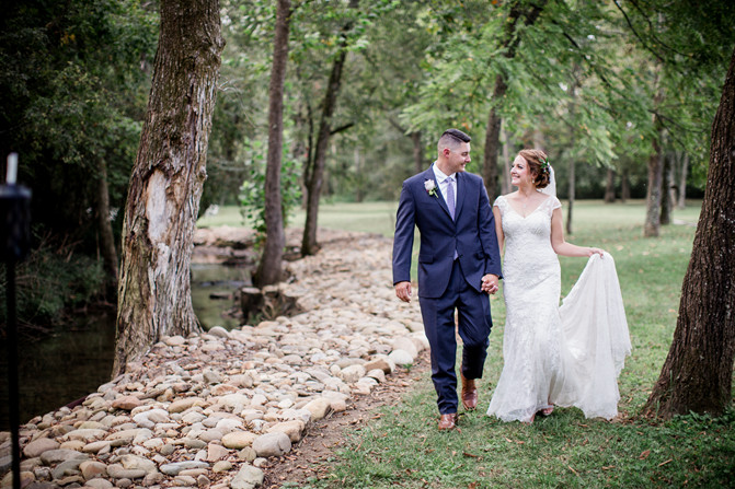 Wedding couple walking by creek at Smithview Pavilion